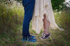 在运动鞋在自然,腿,生活方式概念的时兴的年轻夫妇 库存照片