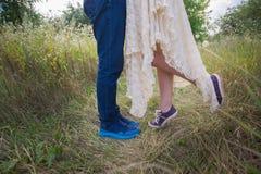 在运动鞋在自然,腿,生活方式概念的时兴的年轻夫妇 免版税库存图片