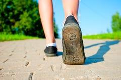 在运动鞋的女性腿关闭跑在路下 免版税库存图片