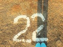 在运动鞋的女性腿在柏油路和第22站立 库存照片