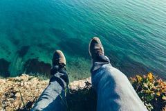 在运动鞋的精神腿在美丽如画的海landscapehiking的旅行松弛概念背景中  库存图片