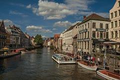 在运河前面的老大厦,有小船和人的在跟特 免版税库存照片