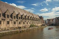 在运河前面的老大厦,有小船和人的在跟特 免版税库存图片
