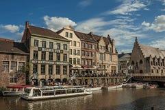 在运河前面的老大厦,有小船和人的在跟特 库存照片