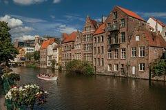 在运河前面的老大厦,有小船和人的在跟特 图库摄影