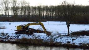 在运河旁边的挖掘机在冬天风景 免版税库存照片