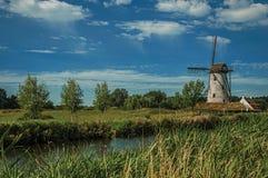 在运河旁边的老风车有灌木的和树丛在下午光和蓝天末期的背景中,在达默附近 免版税库存照片
