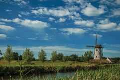 在运河旁边的老风车有灌木的和树丛在下午光和蓝天末期的背景中,在达默附近 库存照片
