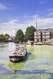 在运河的传统船有绿藻类和一个巨大的豪宅的,荷兰扁圆形干酪,荷兰 库存图片