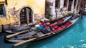 在运河的停放的五颜六色的长平底船在威尼斯,意大利 免版税库存图片