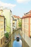 在运河的小船在晴朗的春天d的欧洲大厦之间 免版税库存图片
