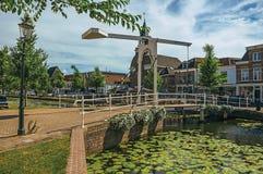 在运河的开启桥有水生植物、街道在银行和房子的在一个晴天在韦斯普 免版税库存照片