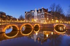 在运河的桥梁在阿姆斯特丹在晚上 免版税库存照片
