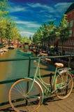 在运河的桥梁有自行车的黏附了在楼梯栏杆并且停泊了小船在蓝天下在阿姆斯特丹 免版税库存图片