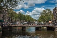 在运河的桥梁有通过在阿姆斯特丹的大厦、人和骑自行车者的 库存图片