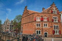 在运河的桥梁有通过在阿姆斯特丹的砖瓦房、人和骑自行车者的 库存照片