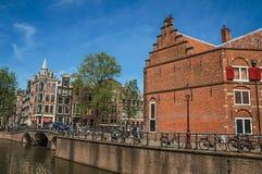 在运河的桥梁有通过在阿姆斯特丹的砖瓦房、人和骑自行车者的 免版税图库摄影