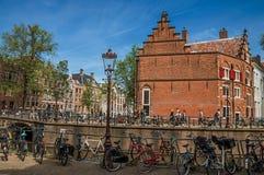 在运河的桥梁有通过在阿姆斯特丹的砖瓦房、人和骑自行车者的 免版税库存图片