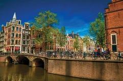 在运河的桥梁有通过在阿姆斯特丹的砖瓦房、人和骑自行车者的 库存图片