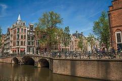 在运河的桥梁有通过在阿姆斯特丹的砖瓦房、人和骑自行车者的 免版税库存照片