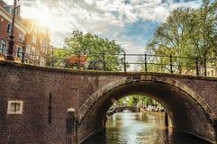 在运河的狭窄的砖桥梁有铁楼梯栏杆和晴朗的天空的在阿姆斯特丹 库存照片