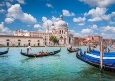 在运河的长平底船重创与大教堂二圣玛丽亚della向致敬,威尼斯,意大利 免版税图库摄影