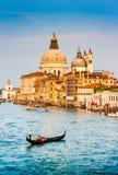 在运河的长平底船重创与大教堂二圣玛丽亚della致敬在日落,威尼斯,意大利 图库摄影