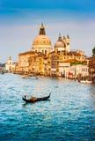 在运河的长平底船重创与大教堂二圣玛丽亚della致敬在日落,威尼斯,意大利 库存图片