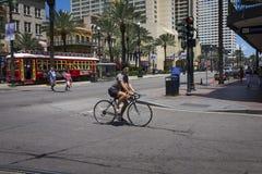 在运河街道的街道场面有一辆自行车的一个人的在市的街市新奥尔良,路易斯安那 免版税库存图片