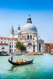 在运河重创与大教堂二圣玛丽亚della致敬,威尼斯,意大利的传统长平底船 免版税库存图片