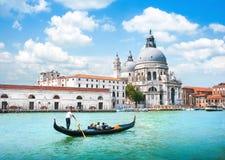 在运河重创与大教堂二圣玛丽亚della致敬,威尼斯,意大利的长平底船 免版税库存照片