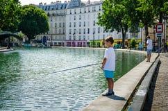 在运河Staint马丁一边的男孩鱼在巴黎 库存照片