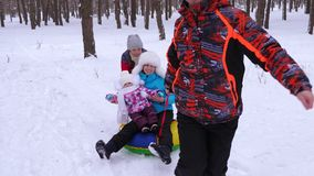 在运行在冬天多雪的森林和笑里的雪茶碟的爸爸卷婴孩和妈妈 男人和妇女有他们的女儿的有 影视素材