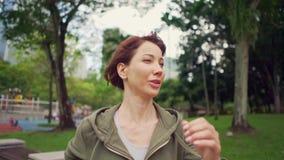 在运行在城市公园的有冠乌鸦的年轻可爱的妇女射击的常平架 影视素材