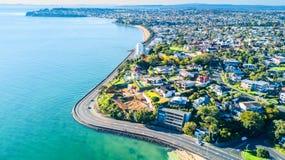 在运行沿与郊区住宅区的海岸的路的鸟瞰图背景的 奥克兰新西兰 免版税库存图片