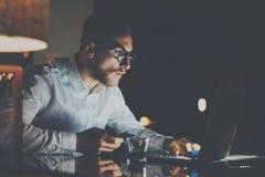 在运转在办公室的镜片的有胡子的年轻商人在晚上 使用当代笔记本的人为短信的消息 免版税库存照片