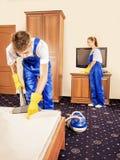 在运转在屋子里的制服的清洁队 免版税库存照片