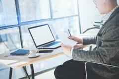 在运转在膝上型计算机的办公室的镜片的商人,当坐在木桌上时 工友anazyle文件 免版税图库摄影