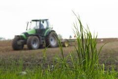在运转的拖拉机背景的绿草  免版税库存图片