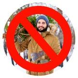 在运载新近地砍的圣诞节杉树和轴的有胡子的伐木工人人的注销的红色标志在森林 免版税库存图片