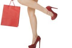 在运载红色袋子的红色高跟鞋的妇女腿 免版税图库摄影
