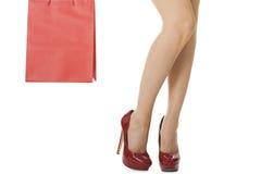 在运载红色袋子的红色高跟鞋的妇女腿 免版税库存照片