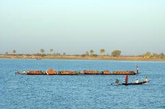 在运载货物河的非洲小船间 库存照片