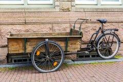 在运输物品的自行车框架修造的木手车通过阿姆斯特丹 免版税库存图片