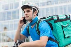 在运送食物的自行车的传讯者在城市使用手机 免版税库存图片