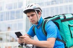 在运送食物的自行车的传讯者在城市使用手机 免版税库存照片
