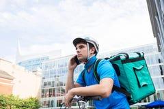 在运送食物的自行车的传讯者在城市使用手机 库存照片