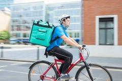 在运送食物的自行车的传讯者在城市 免版税库存图片