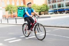 在运送食物的自行车的传讯者在城市 库存照片