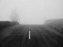 在近大雾的乡下公路在小山的上面 免版税库存图片